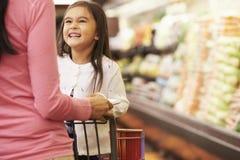 Ciérrese para arriba de la madre que empuja a la hija en carretilla del supermercado Imágenes de archivo libres de regalías