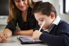 Ciérrese para arriba de la maestra joven que se sienta en el escritorio con un colegial de Síndrome de Down que usa una tableta e imagen de archivo