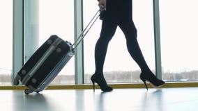 Ciérrese para arriba de la maleta que lleva de la mujer en el terminal de aeropuerto y apresúrese para arriba para el incorporar  almacen de metraje de vídeo