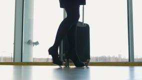 Ciérrese para arriba de la maleta que lleva de la mujer en el terminal de aeropuerto y apresúrese para arriba para el incorporar  almacen de video