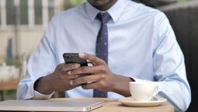 Ciérrese para arriba de la mano africana usando Smartphone almacen de video