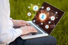 Ciérrese para arriba de la mano con el ordenador portátil y los medios iconos sociales Imágenes de archivo libres de regalías