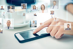 Ciérrese para arriba de la mano con smartphone y los contactos fotografía de archivo libre de regalías