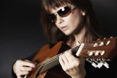 Ciérrese para arriba de la mano de la muchacha que toca la guitarra. imagen de archivo libre de regalías