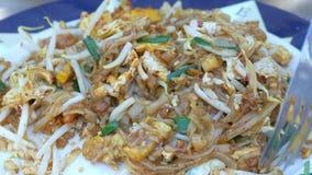 Ciérrese para arriba de la mano de la mujer que come los tallarines de arroz sofritos tailandeses del cojín con los huevos y las  almacen de video