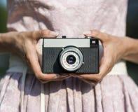 Ciérrese para arriba de la mano de la mujer que sostiene la cámara retra Foto de archivo