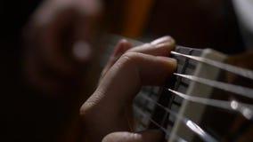 Ciérrese para arriba de la mano del guitarrista que toca la guitarra acústica Ciérrese encima de tiro de un hombre con sus finger almacen de metraje de vídeo