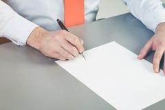 Ciérrese para arriba de la mano del hombre de negocios que se prepone escribir un documento, una petición o una demanda Un concep fotos de archivo libres de regalías