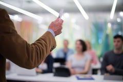 Ciérrese para arriba de la mano del profesor mientras que enseña en sala de clase Fotos de archivo