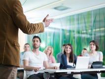 Ciérrese para arriba de la mano del profesor mientras que enseña en sala de clase Imagen de archivo
