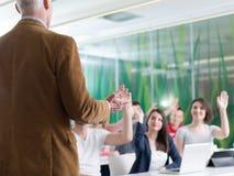 Ciérrese para arriba de la mano del profesor mientras que enseña en sala de clase Fotografía de archivo libre de regalías