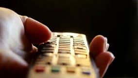 Ciérrese para arriba de la mano del ` s de la mujer con los canales cambiantes teledirigidos de una televisión en el tiempo de la almacen de metraje de vídeo