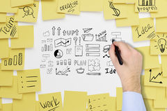 Ciérrese para arriba de la mano del ` s del hombre de negocios que dibuja un bosquejo de lanzamiento de la idea encendido Foto de archivo libre de regalías