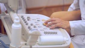 Ciérrese para arriba de la mano del ` s del doctor que manipula alrededor de la palanca de mando de una consola del ultrasonido metrajes
