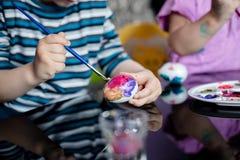Ciérrese para arriba de la mano del ` s del muchacho que sostiene el huevo y el cepillo, coloreando eggs para Pascua Imagenes de archivo