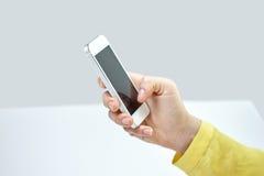 Ciérrese para arriba de la mano femenina con smartphone en casa Imagenes de archivo