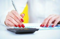 Ciérrese para arriba de la mano femenina del contable o del banquero que hace cálculos Ahorros, finanzas y concepto de la economí fotos de archivo libres de regalías