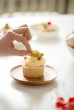 Ciérrese para arriba de la mano femenina que adorna una magdalena con la hoja de la menta Imagen de archivo