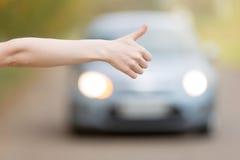 Ciérrese para arriba de la mano femenina que hace autostop fotografía de archivo libre de regalías