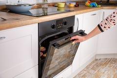 Ciérrese para arriba de la mano de las mujeres que abre la puerta del horno para controlar la carne asada fotografía de archivo libre de regalías