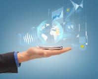 Ciérrese para arriba de la mano masculina con smartphone y el holograma Fotografía de archivo