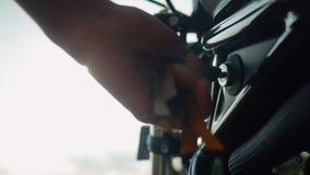 Ciérrese para arriba de la mano masculina que consigue dominante fuera de la moto metrajes
