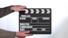 Ciérrese para arriba de la mano masculina que sostiene clapperboard de la película metrajes