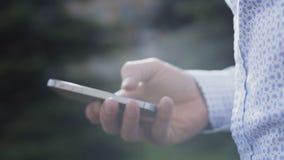 Ciérrese para arriba de la mano masculina usando smartphone en fondo 4K metrajes