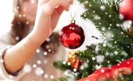 Ciérrese para arriba de la mano de la mujer que adorna el árbol de navidad Imágenes de archivo libres de regalías