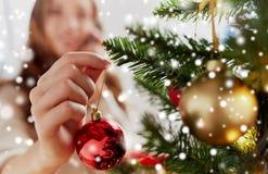 Ciérrese para arriba de la mano de la mujer que adorna el árbol de navidad Imagenes de archivo
