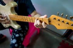 Ciérrese para arriba de la mano de la mujer que toca la guitarra eléctrica Foto de archivo libre de regalías