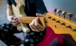 Ciérrese para arriba de la mano de la mujer que toca la guitarra eléctrica Fotos de archivo