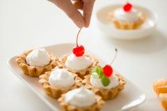 Ciérrese para arriba de la mano que adorna mini tartas poner crema con la cereza Imagenes de archivo