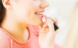 Ciérrese para arriba de la mano que aplica el lápiz labial a los labios de la mujer Fotografía de archivo libre de regalías