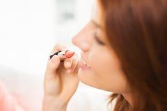 Ciérrese para arriba de la mano que aplica el lápiz labial a los labios de la mujer Imagenes de archivo