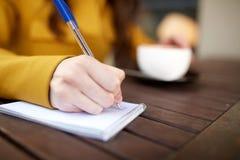 Ciérrese para arriba de la mano que escribe al cuaderno en el café Fotos de archivo libres de regalías