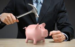 Ciérrese para arriba de la mano que guarda el martillo sobre poco moneybox Fotografía de archivo libre de regalías