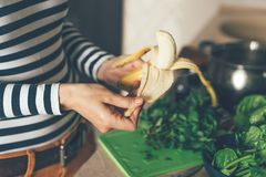 Ciérrese para arriba de la mano que pela un plátano fotografía de archivo
