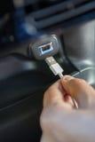 Ciérrese para arriba de la mano que sostiene el conector USB en coche Fotos de archivo libres de regalías