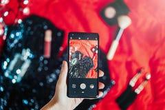 Ciérrese para arriba de la mano que sostiene el teléfono móvil que hace las fotos del vestido de cóctel fotografía de archivo