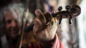 Ciérrese para arriba de la mano de un hombre que toca un violín Fotografía de archivo libre de regalías