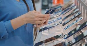 Ciérrese para arriba de la mano de una mujer que sostiene un nuevo smartphone cerca del escaparate en una tienda de la electrónic almacen de metraje de vídeo