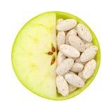 Ciérrese para arriba de la manzana y de las píldoras aisladas Imagen de archivo