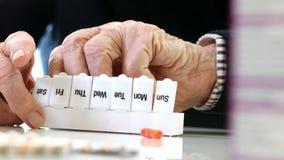 Ciérrese para arriba de la medicación de organización del hombre mayor en dispensador de la píldora almacen de metraje de vídeo