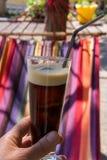 Ciérrese para arriba de la mentira femenina de la mano de la mujer en la hamaca que sostiene el vidrio de café frío foto de archivo