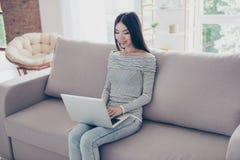 Ciérrese para arriba de la muchacha asiática feliz joven que mecanografía en su ordenador portátil, sentándose Fotos de archivo libres de regalías