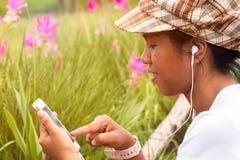 Ciérrese para arriba de la muchacha asiática que juega Internet y música que escucha del teléfono móvil en parque bajo luz calien Fotografía de archivo