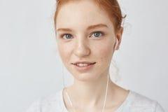 Ciérrese para arriba de la muchacha del pelirrojo en auriculares que sonríe mirando la cámara Imagen de archivo