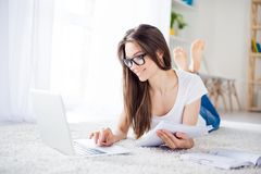 Ciérrese para arriba de la muchacha feliz joven que mecanografía en su ordenador portátil que miente en la f Imagenes de archivo