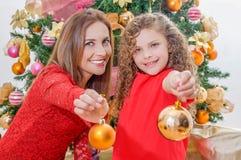 Ciérrese para arriba de la muchacha feliz que adorna el árbol de navidad con su mamá que señala delante de ellos las bolas de oro Fotografía de archivo libre de regalías